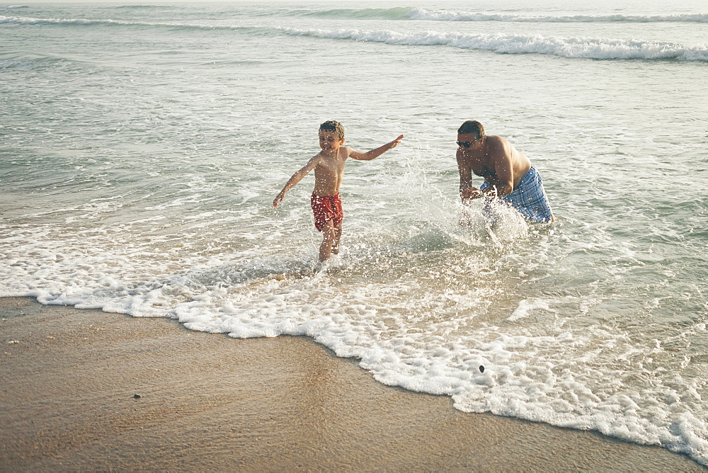 Father splashing son on beach