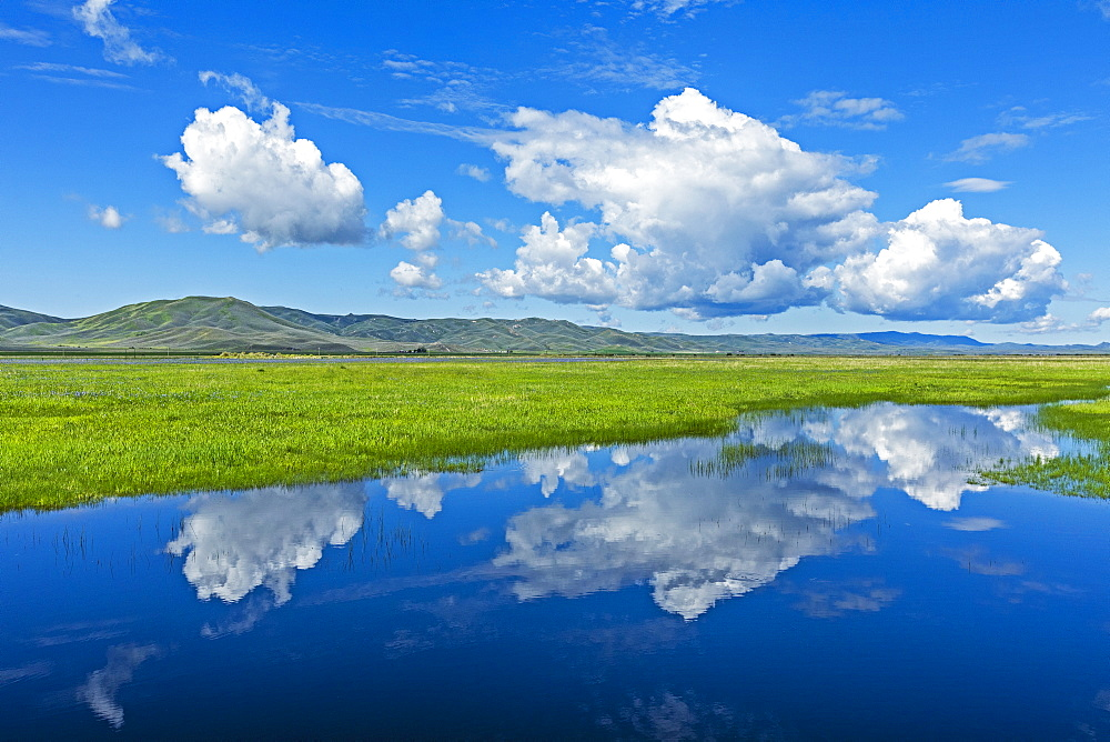 Clouds over river through fields in Fairfield, Idaho, USA