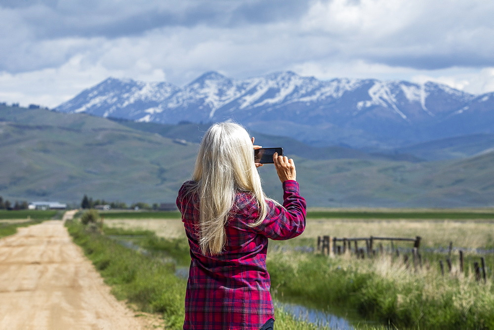 Woman photographing mountains in Fairfield, Idaho, USA