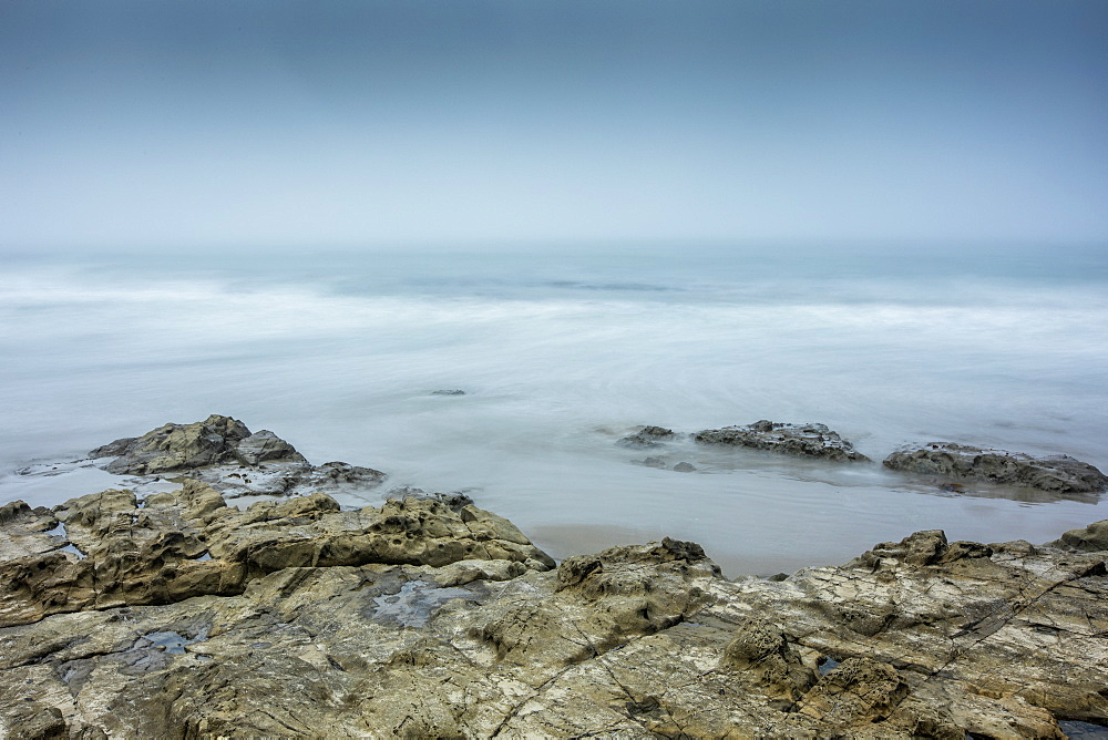 Long exposure shot of rocks on beach in Morro Bay, California, USA