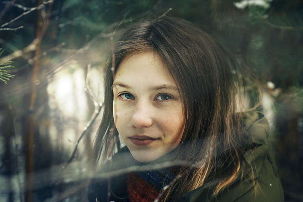 Teenage girl amongst pine branches in winter