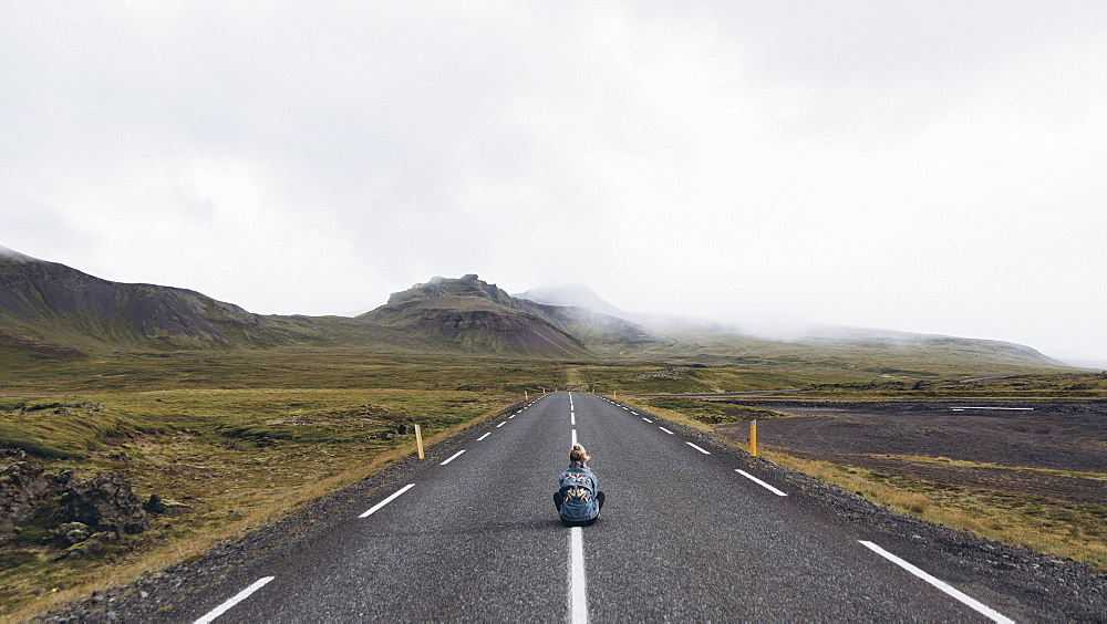 Woman sitting on highway in Iceland