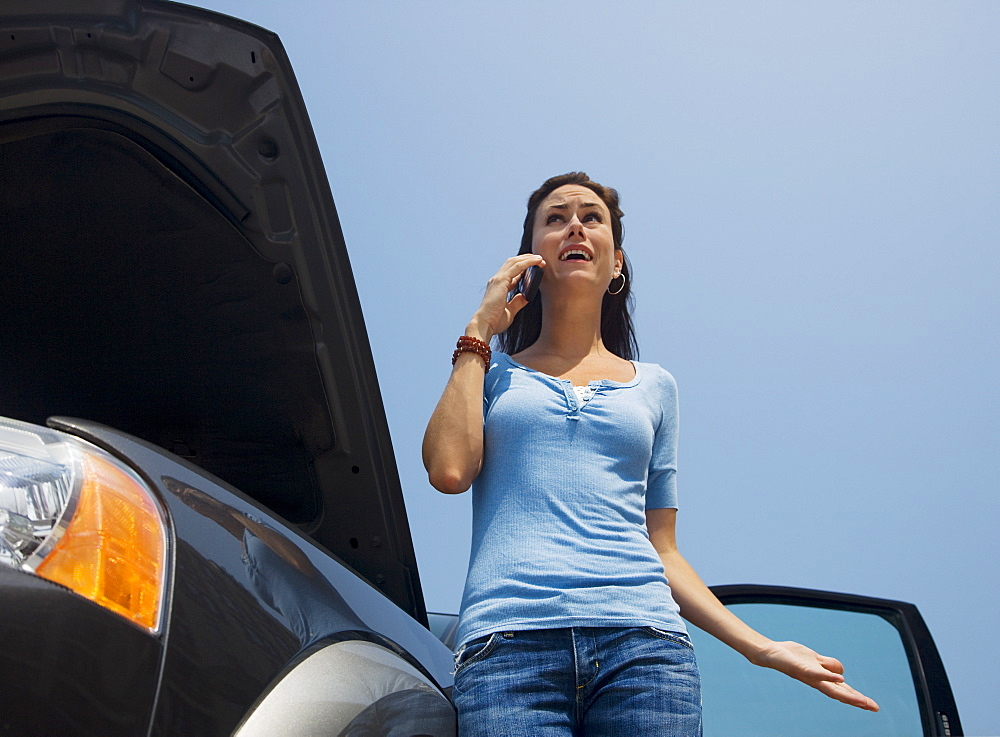 Woman talking on cell phone next to broken down car