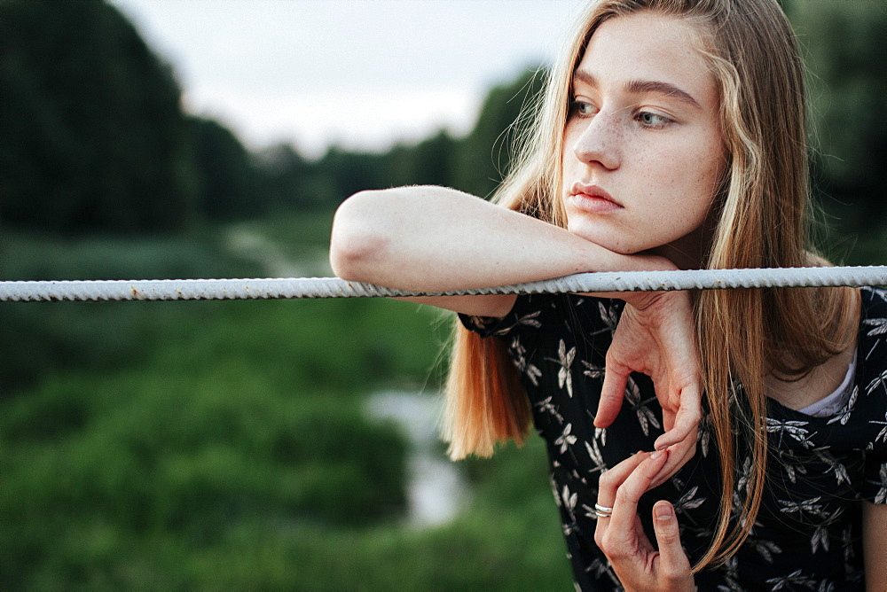 Young woman leaning on metal fence