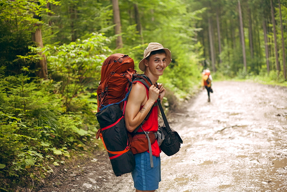 Young man hiking in forest at the Carpathian Mountain Range, Ukraine