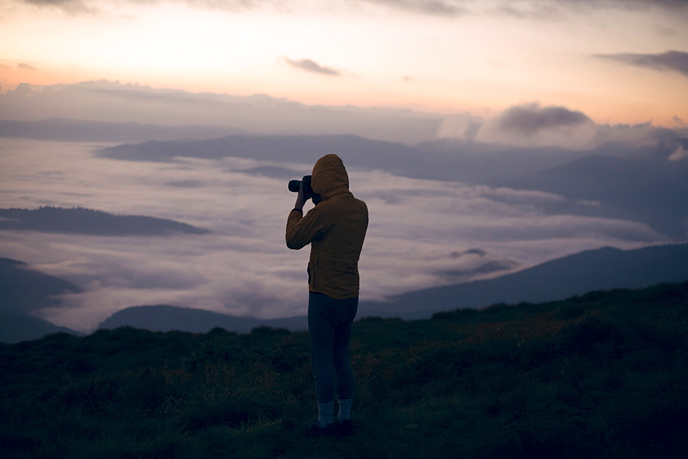 Silhouette of young man taking photographs at sunset in the Carpathian Mountain Range