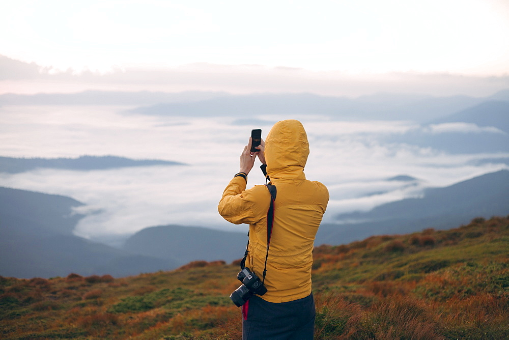 Man in yellow jacket taking photograph on smart phone in the Carpathian Mountain Range