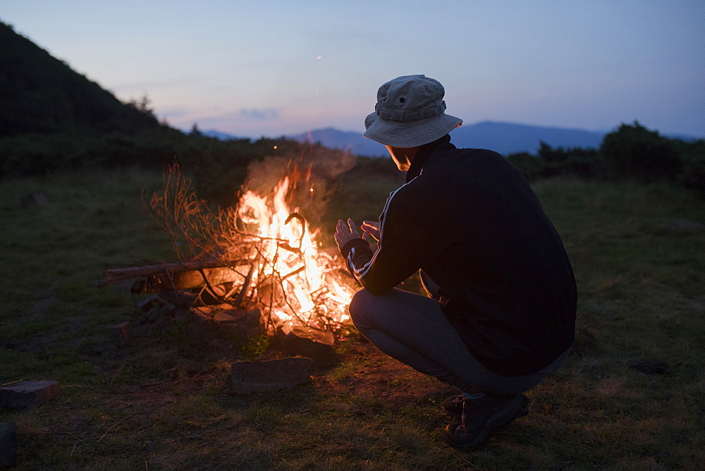 Man crouching by campfire