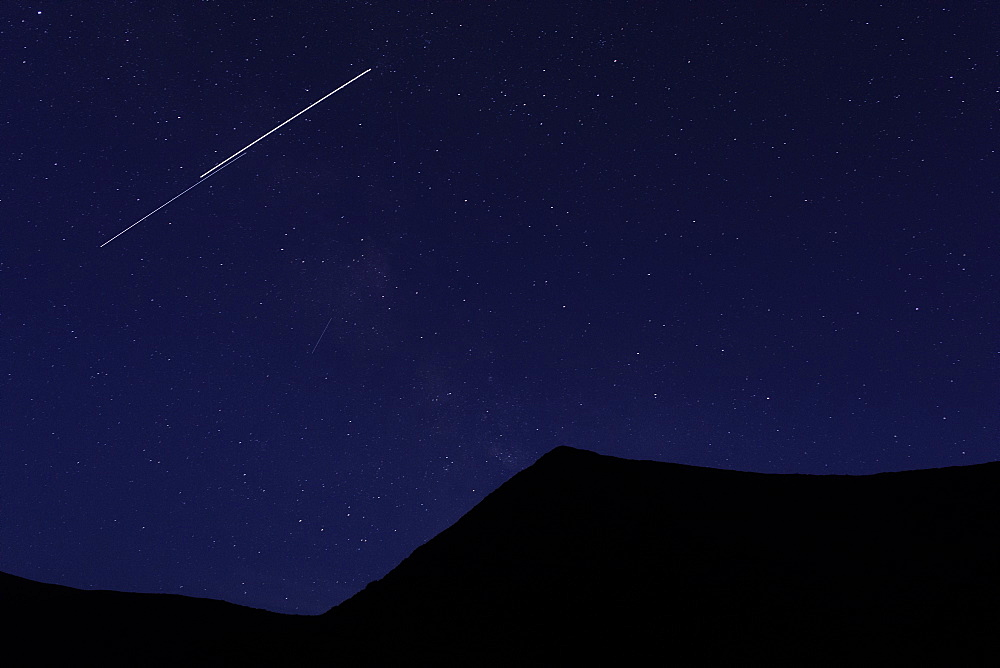Shooting star above silhouette of mountain