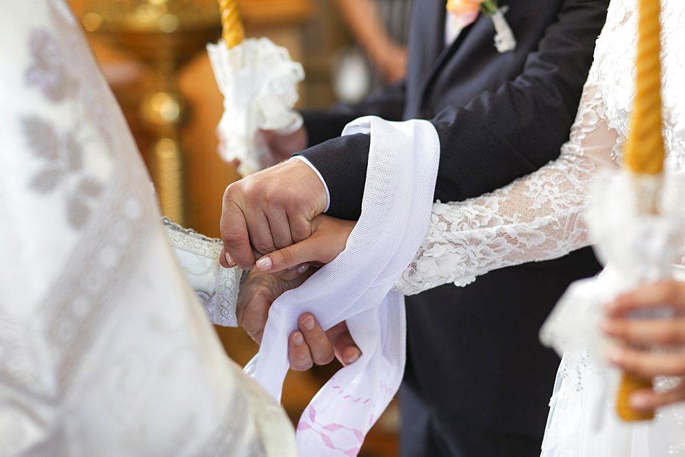 Hands of bride and groom tied together during wedding ceremony