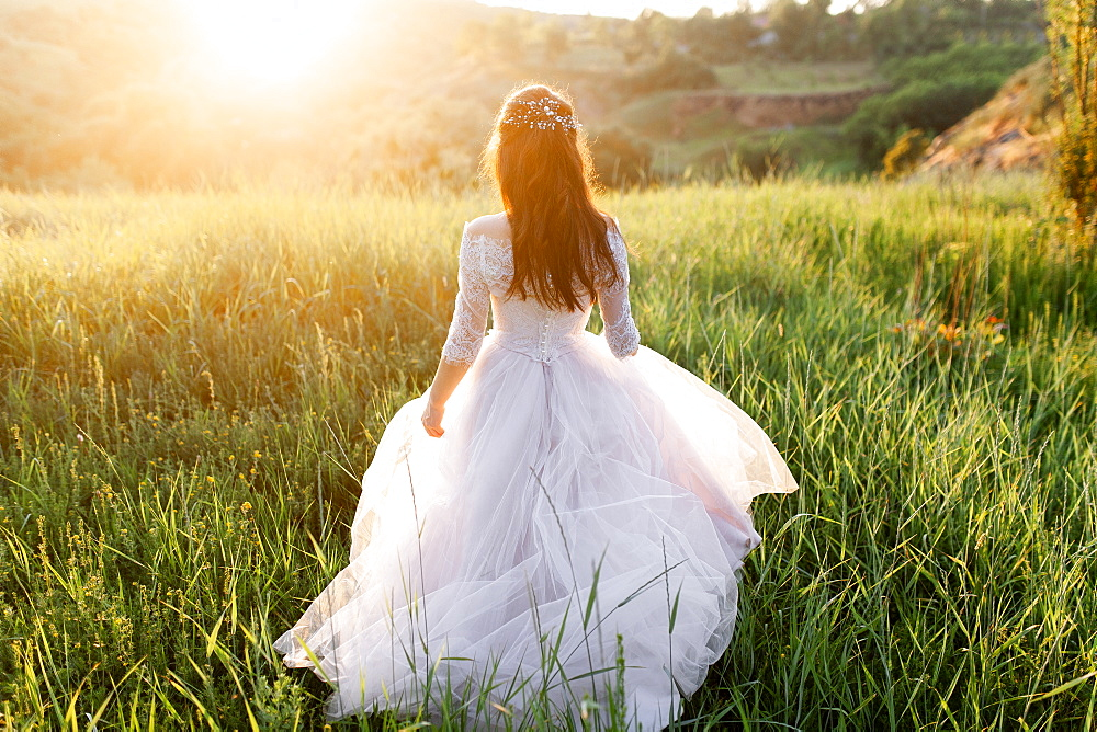 Rear view of bride in wedding dress walking in grass