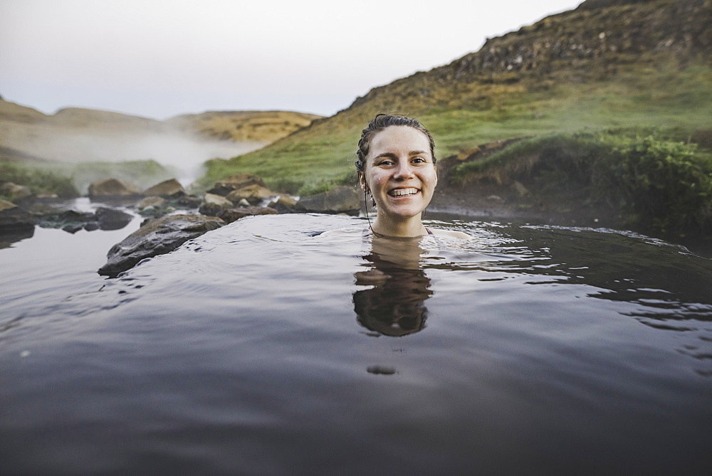 Woman bathing in hotpool in Iceland