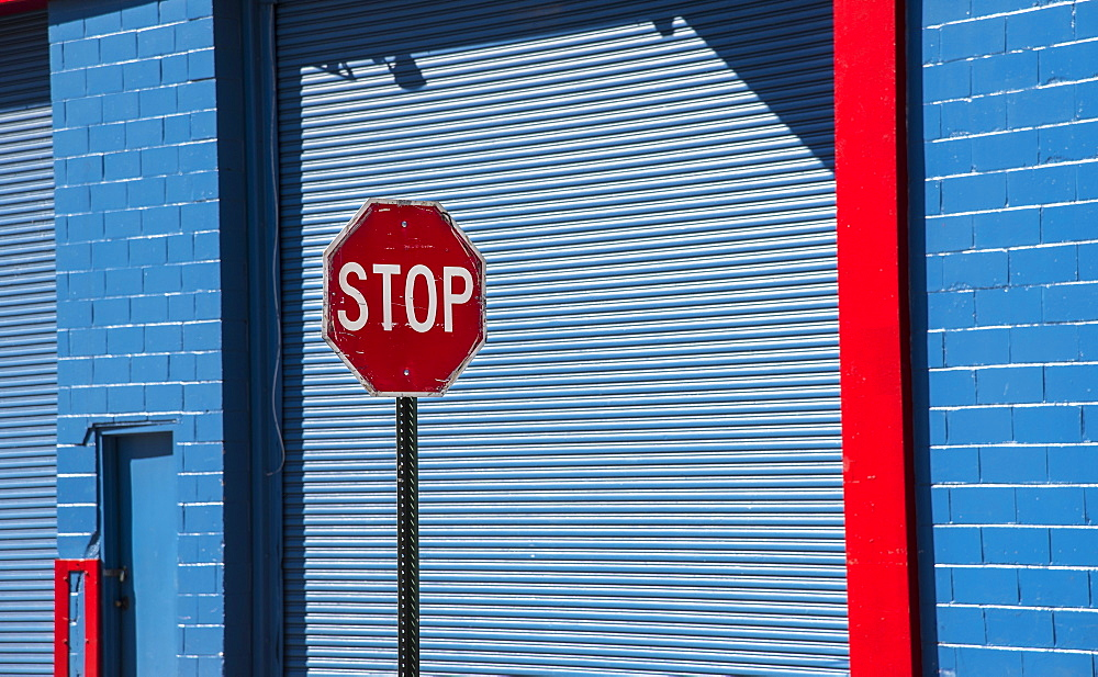 Stop sign by blue garage door