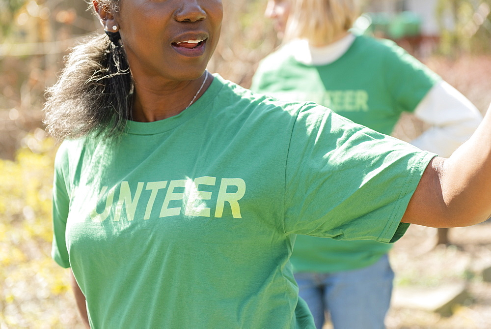 Mature woman volunteer in green t-shirt