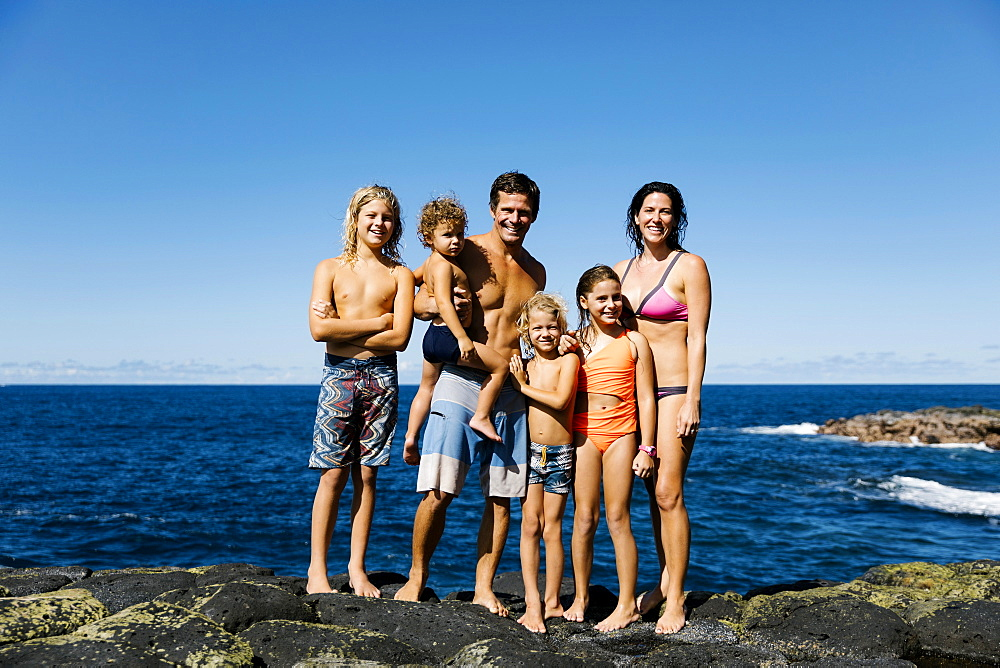 Smiling family standing on rocks by sea