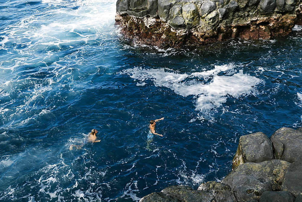 Father and son swimming in sea by cliffs