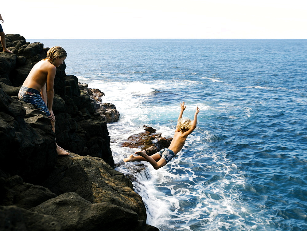 Boy jumping off cliff by sea