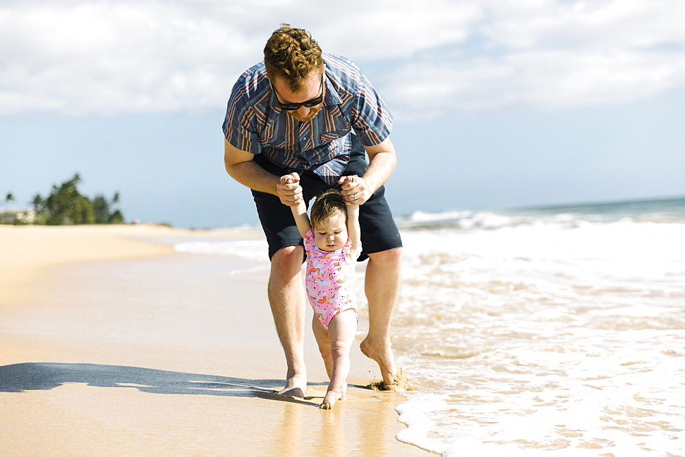 Father helping his baby girl walk on beach