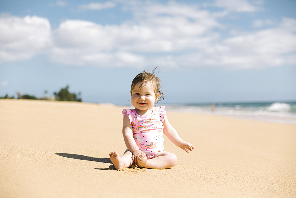 Baby girl wearing pink swimwear sitting on beach