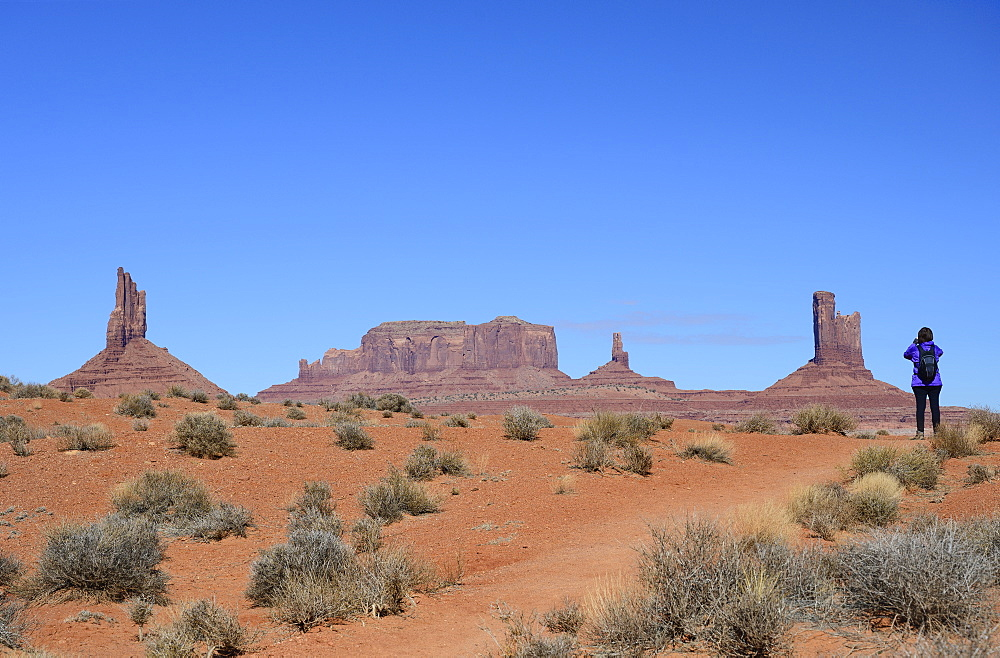 Woman wearing backpack by buttes in Monument Valley, Arizona, USA