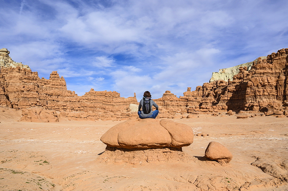 Woman sitting on rock in Goblin Valley State Park, Utah, USA