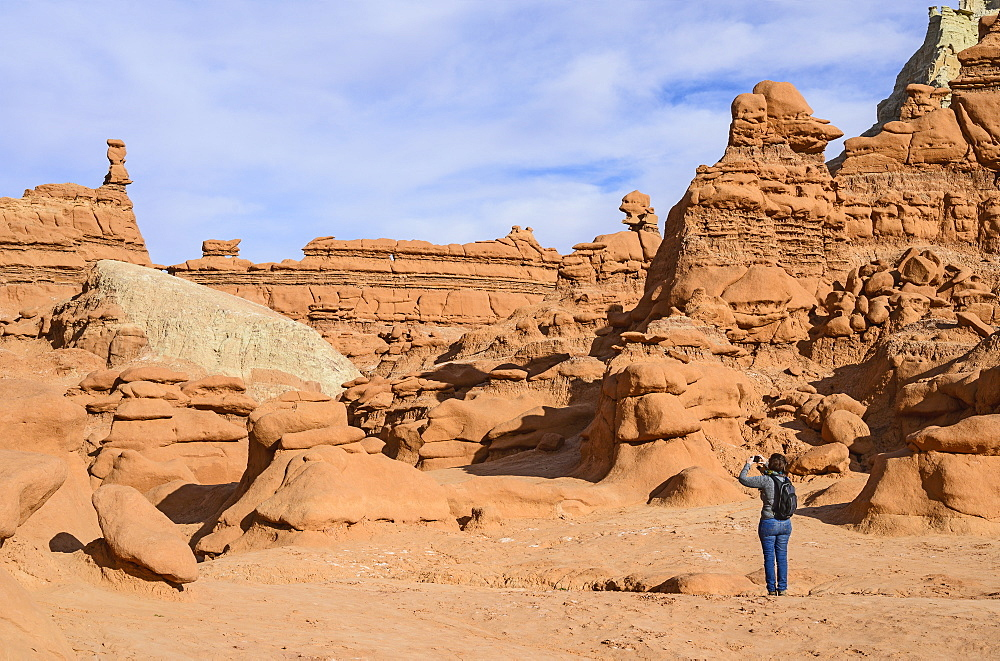 Woman photographing hoodoos in Goblin Valley State Park, Utah, USA
