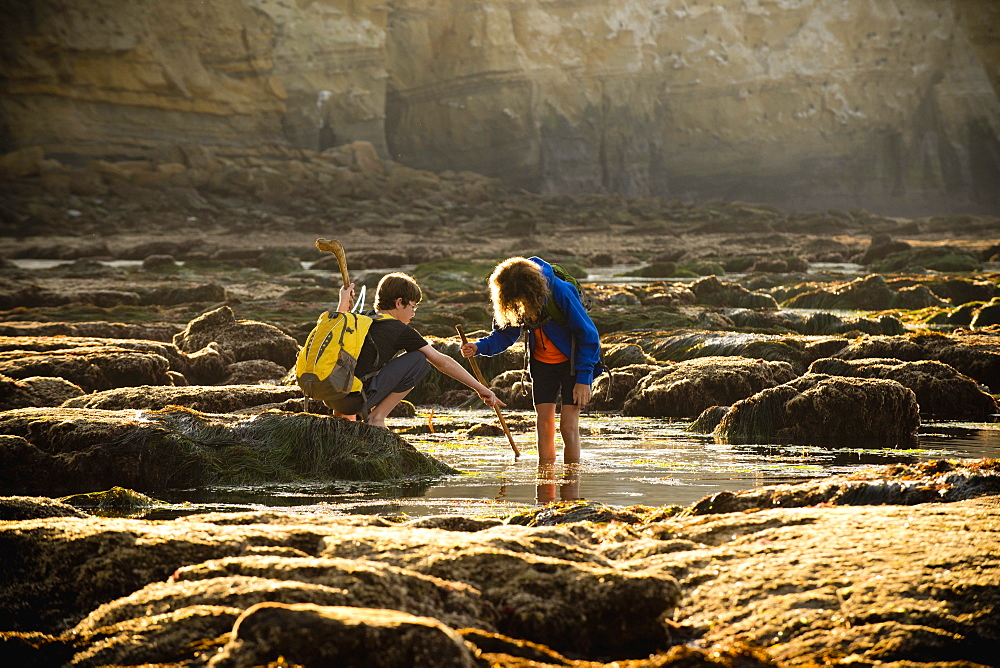 Teenage boys on rocks by tide pool in La Jolla, California