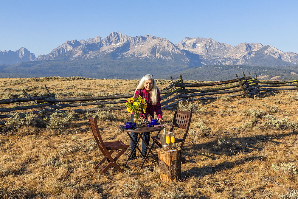 Mature woman setting dining table in field by mountain in Stanley, Idaho
