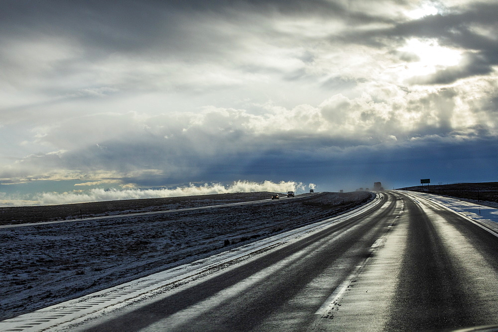 Country road with snow under overcast sky