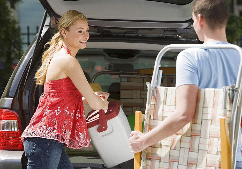 Couple loading vacation items into truck