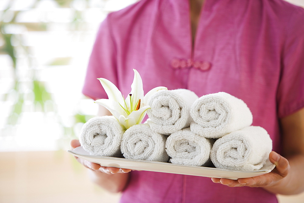Woman holding tray of rolled towels - 1178-2701