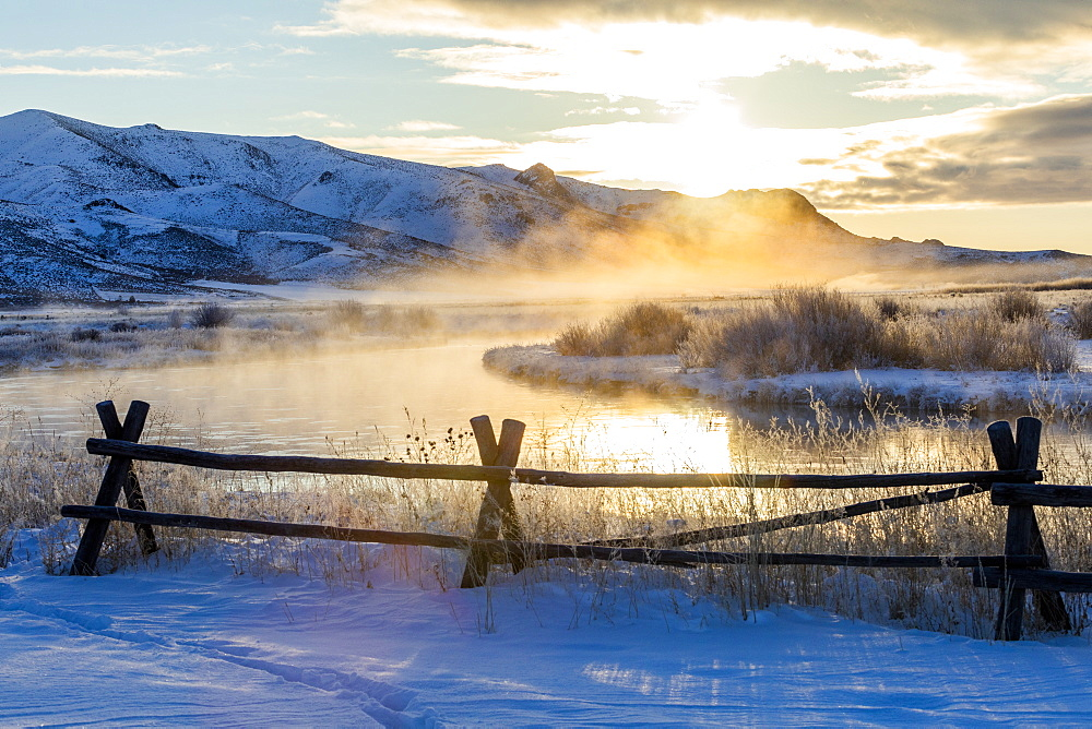 Fence by river at sunrise in Picabo, Idaho
