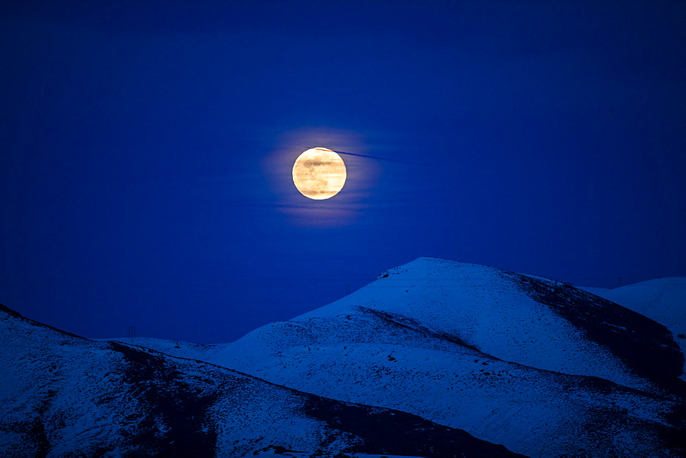 Full moon over mountains at night in Bellevue, Idaho, USA