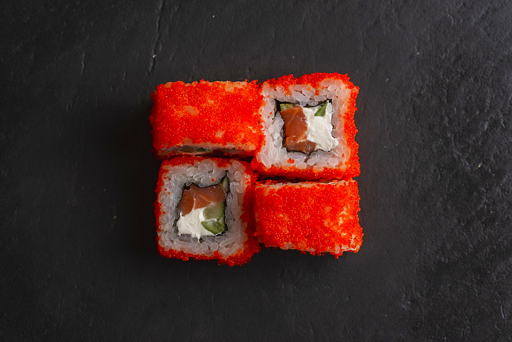 Red fish roe sushi on black surface