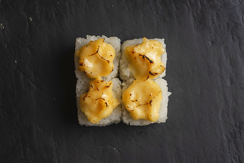Sushi with burnt yellow sauce