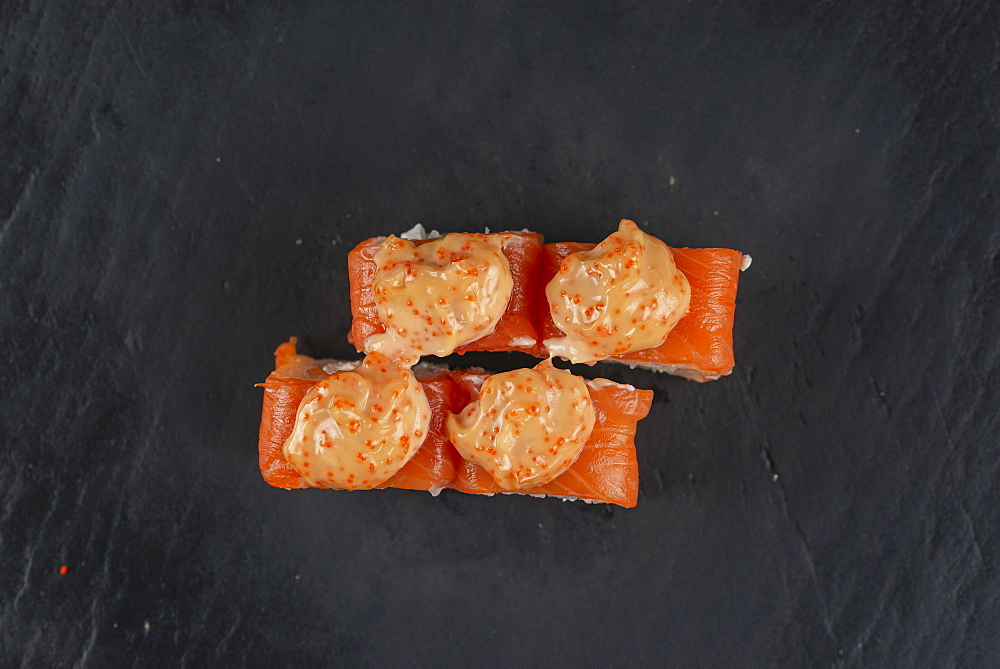Salmon sushi with orange sauce