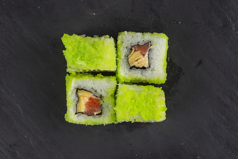 Green fish roe sushi on black surface