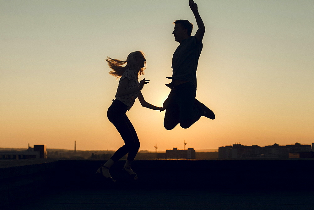 Silhouettes of young couple jumping at sunset