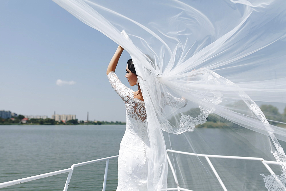 Bride with windswept veil on boat