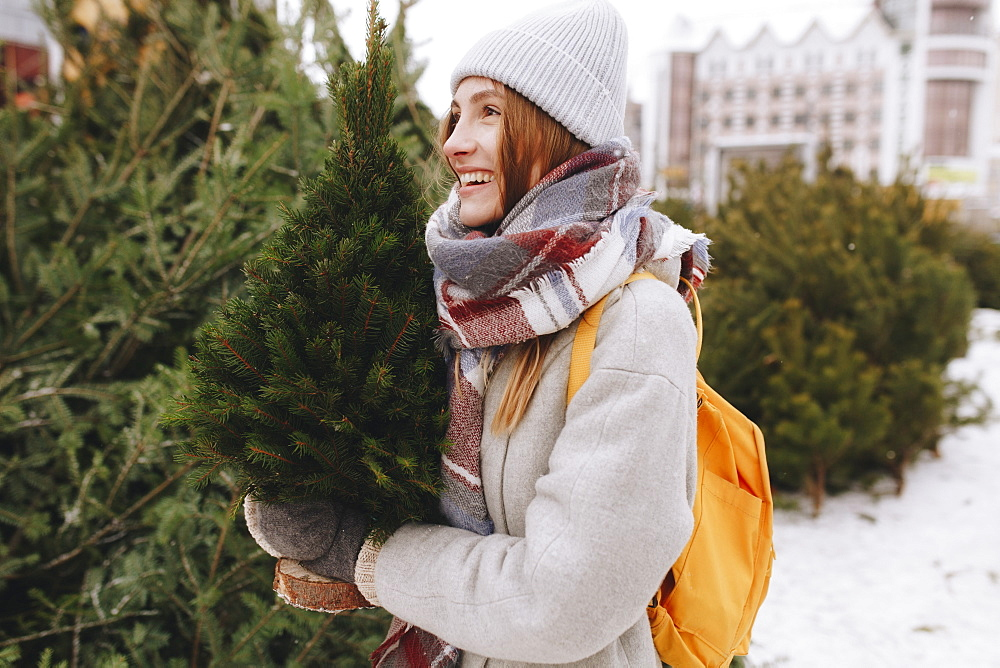 Young woman carrying small Christmas tree