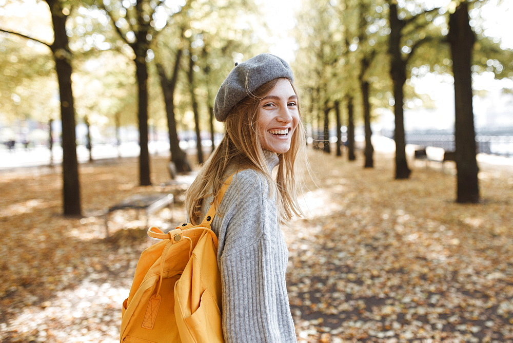 Young woman with yellow backpack in park in Berlin, Germany