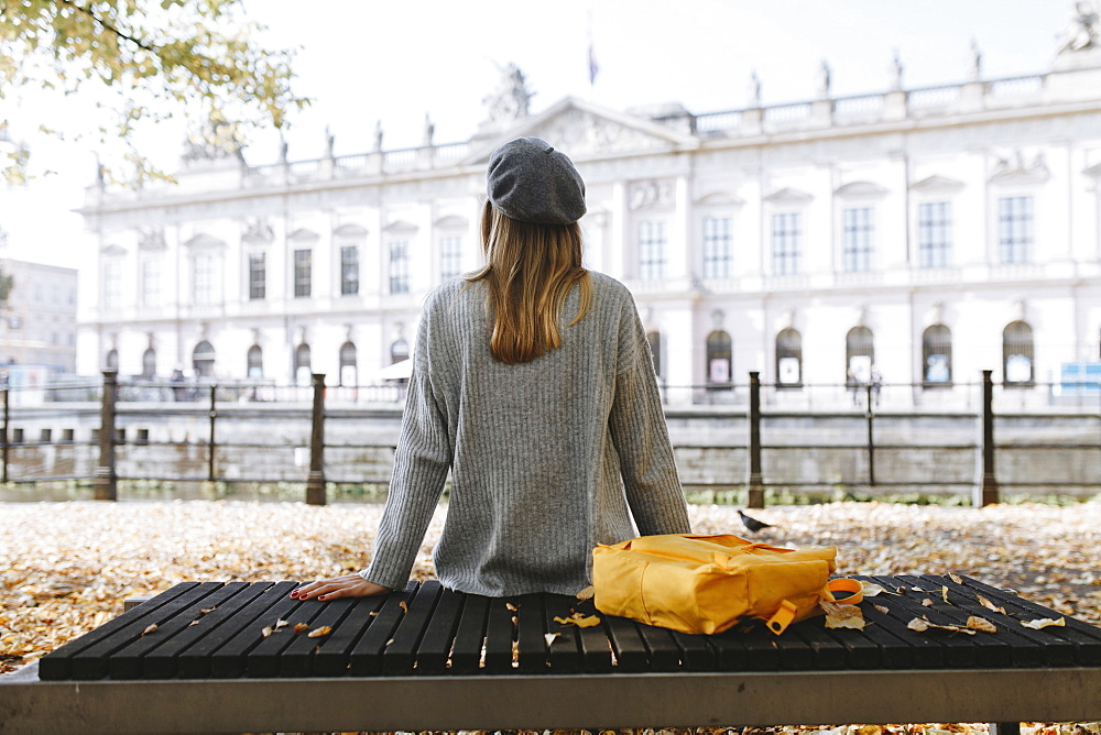 Young woman sitting on park bench near German Historical Museum in Berlin, Germany