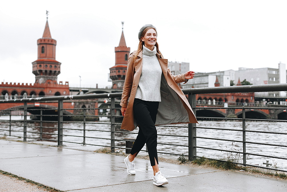 Young woman walking by river in Berlin, Germany