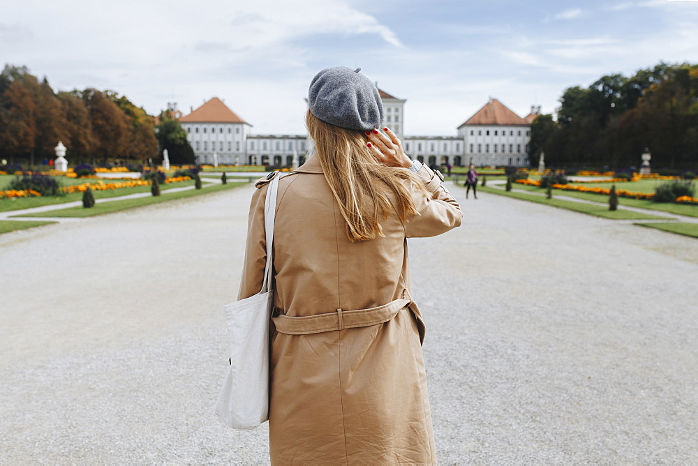 Woman wearing coat and beret by Nymphenburg Palace in Munich, Germany