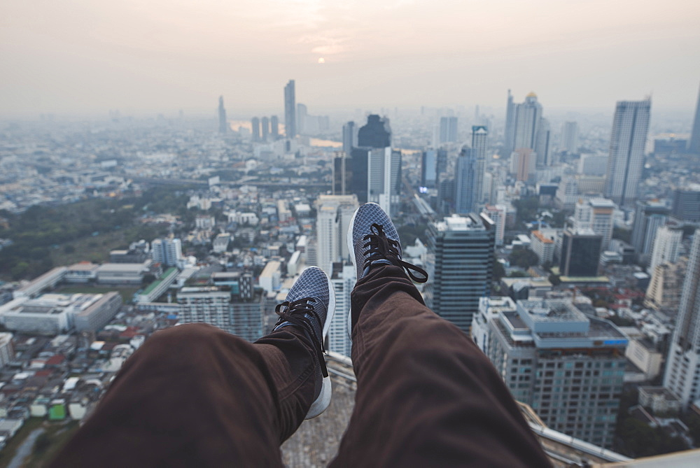 Legs of young man and cityscape of Bangkok, Thailand