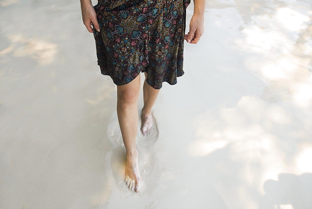 Legs of woman walking on beach