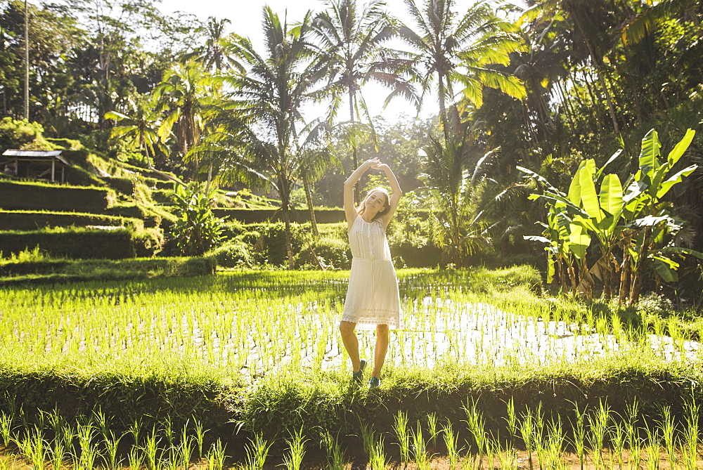 Young woman wearing white dress in rice paddy in Bali, Indonesia