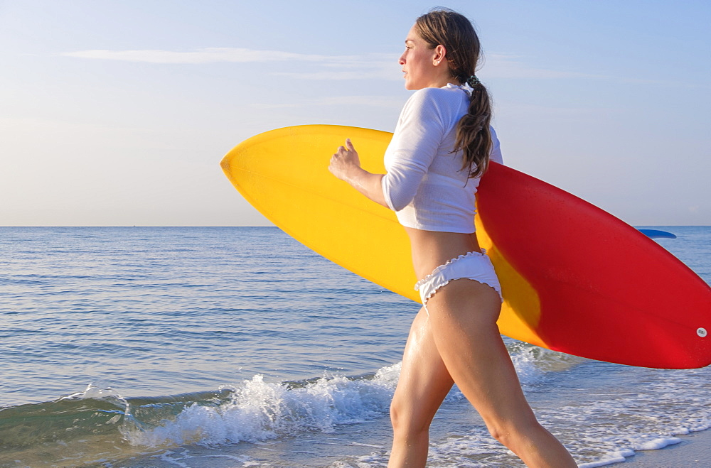 Woman holding surfboard running into sea