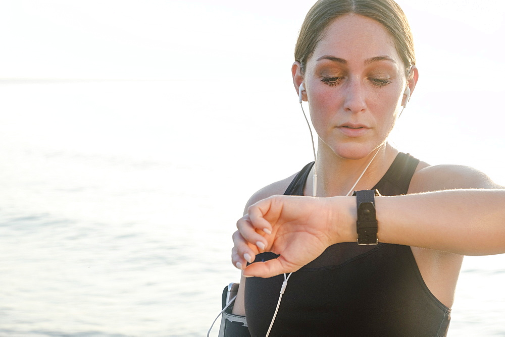 Woman wearing headphones checking wrist watch on beach