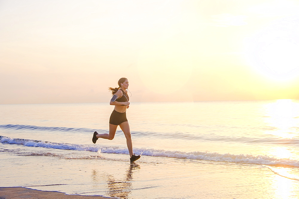 Woman jogging on beach at sunset